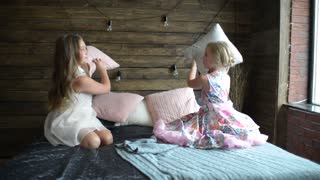 Two girls sisters fighting pillows on the bed