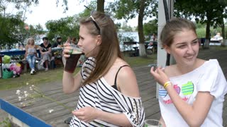 Two girls sitting in a park and drinking dark beer
