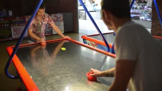 Two Men playing air hockey in the amusement park