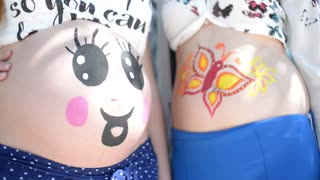 Two Pregnant female belly And Body Art Artist - at the Park sunny day