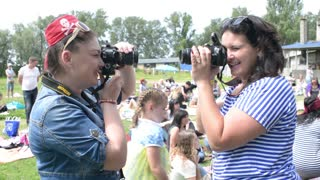 Two women taking pictures of each other on SLR cameras - the summer park