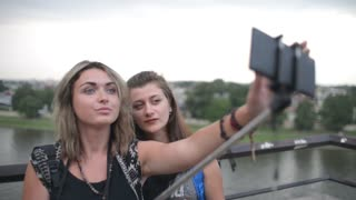 Two Young Beautiful Girls take Selfie Photo by Mobile phone and Stick