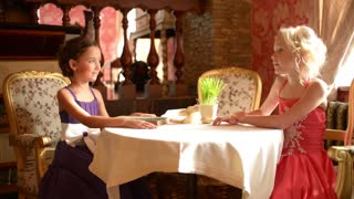 Two young girls in elegant dresses talking at a table in a restaurant