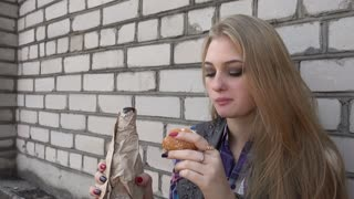 Upset drunk Girl Blonde drinking Beer from a Bottle against the Wall