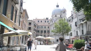 Venice in Summer. People walk along the cafes and souvenir shops