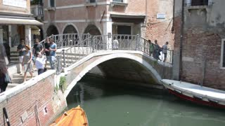 Venice. People walk across the bridge over canal