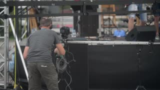 Video equipment slider with the camera and crane works at a concert in front of