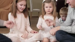 A big Family Mom, Dad with Kids Daughters play a Hand Game at Home fun together