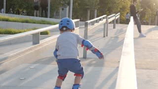 A Boy Kid skates riding Rollers in the City Embankment in sunny Day