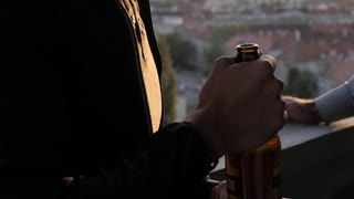 A Latino Man drinking Beer on a Balcony in Evening City