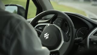 A man drives Suzuki, turn the steering wheel of a vehicle