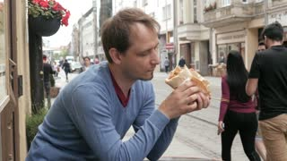 A Man eating Doner Kebab on the Street of an Old European City