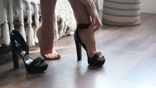 A Woman removes high-heeled Shoes from her Feet and rubs her tired Legs