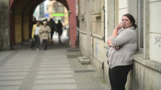 A Woman Smokes Cigarette on Crowded Street - Day Wroclaw Poland