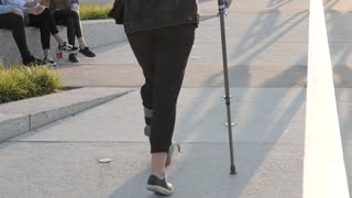 A Woman with Gypsum on her Foot walking with Cane in the City Park