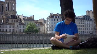 A young boy learns actor role near Seine in Paris - romantic place in summer day