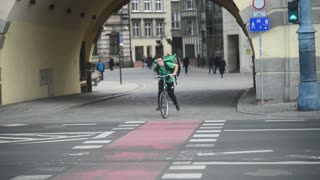 A young Guy delivers a Pizza on a Bicycle on the street of City Wroclaw