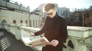 A young Man reads a nationalist Newspaper 'Nation' on the Street of Kiev Ukraine