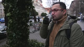 A Young Man Student from India drink Coffee on the Winter Street in Europe