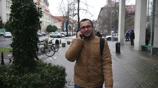 A Young Man Student from India talk to the Phone on the Winter Street in Europe