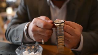 An indian Businessman wrists watches sitting in a cozy Cafe