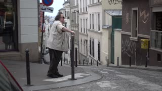 An old man with a cane walking on the streets of Montmartre in Paris