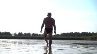 An old senior Man walk in the Lake Water, rubbed with Clay Mud