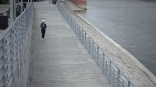 Athletic woman jogging along river in the city Wroclaw Poland