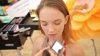 Beautician Applying Makeup Powder To A Beautiful young Model