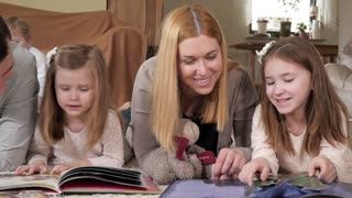 Big Happy Family read Books with Fairy Tales for Children lying on a Home Floor