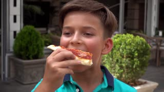 Boy eating Pizza Margarita by Hands