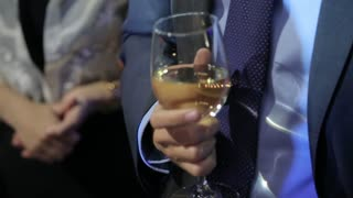 Business Man holds a Glass of white Wine in his Hand at a Party