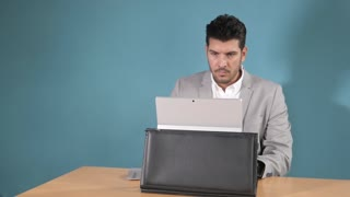 Business Man working with Netbook pc, grey Suit, blue Wall
