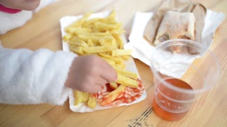 Child girl eating Potato Fries with Tomato Ketchup at the Table Street Food Fest