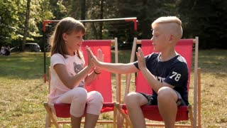 Children Kids Boy and Girl playing clapping Hands counting game in a Park