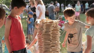 Children Kids play build a Tower with wooden Sticks Jenga in a Park Fest