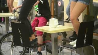 Children teenagers legs dancing on Chairs near Ice Cream Shop