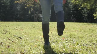 Close-up Legs - Woman dancing in a Park - Blue Jeans and high Boots