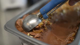 Close Up milk Chocolate Ice Cream Scooping Out Of Container to a Cone