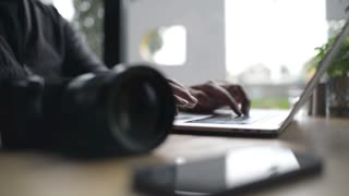 Close-up of a Man Hands use Laptop and Sony Camera at Cafe Table