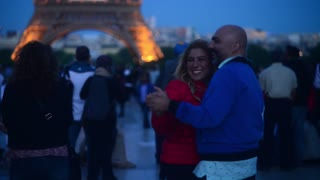 Couple dancing near Eiffel Tour in evening - romantic Paris
