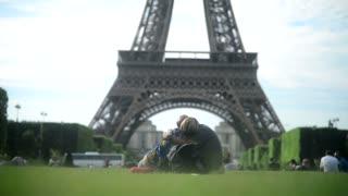 Couple kissing under Eiffel Tour sitting on Grass Champs-de-Mars Paris evening