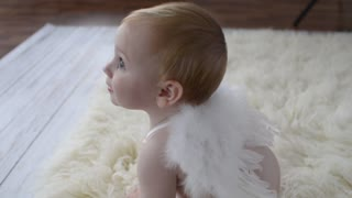 Cute little Baby Girl posing on a Photo Session in Studio as Angel