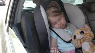 Cute Little Child Girl sleeps in a Car Chair - Hot Summer Day