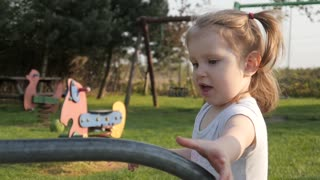 Cute little Girl Child play with Carousel on a Playground - Spring Day