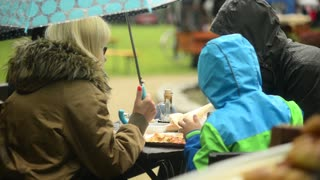 Family eating under Umbrella under the Rain in a Autumn Park Food Cafe - Wroclaw