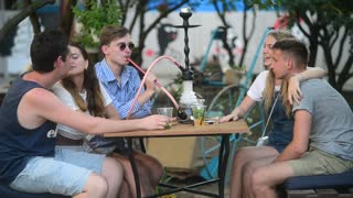 Friends sitting at the Table in Street Hookah Bar, smoke talk and laugh