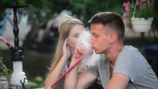 Friends sitting in Street Hookah Bar, Man smokes talk and laugh
