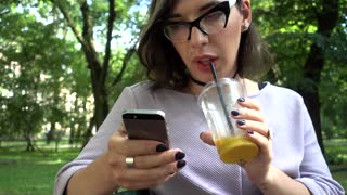 Girl-boy, transgender guy chatting iphone network, drink orange juice in Park