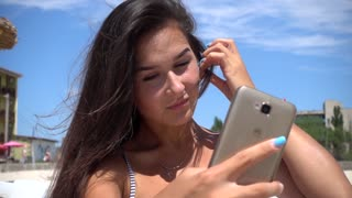 Girl Brunette take Selfie Photo with Smart Phone on the Sea Beach